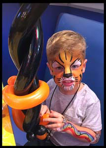 This child looks ferocious with tiger face painting plus body painting Brooklyn nyc