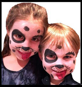 Brother and sister facepainted as dalmations at company party in Manhattan NYC