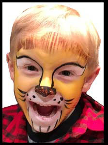 Boy roars in delight at being face painted as lion at restaurant Kids Night entertainment nyc!