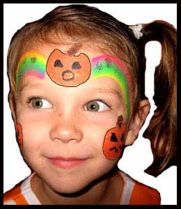 Child gets facepainted with rainbow pumpkin crown at halloween party in New York City