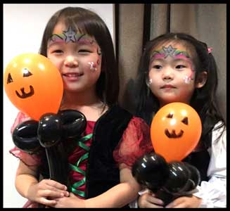 2 girls show off their halloween facepainting and twisted balloons at kids halloween party in New Jersey