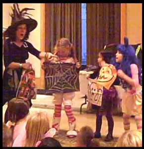 Children volunteers help decorate in Daisy Doodle's magic show for company halloween party in Manhattan NY
