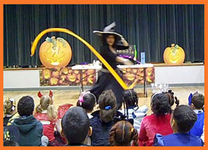 Daisy Doodle dances to music with props at beginning of kids halloween party magic show