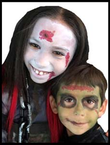 Brother and sister get facepainted to match their costumes at halloween birthday party in Brooklyn NY
