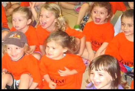 Kids laughing and participating in Daisy Doodle's summer camp magic show in New York City