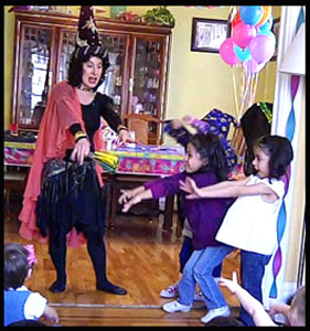 Children help Daisy Doodle at wizard magic show by waving their fingers and saying the magic word