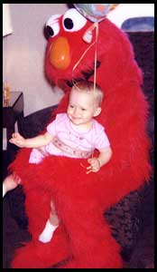 Babies like being held by Elmo character at their birthday party